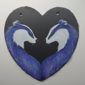 Painting of two badgers facing each other on a slate heart