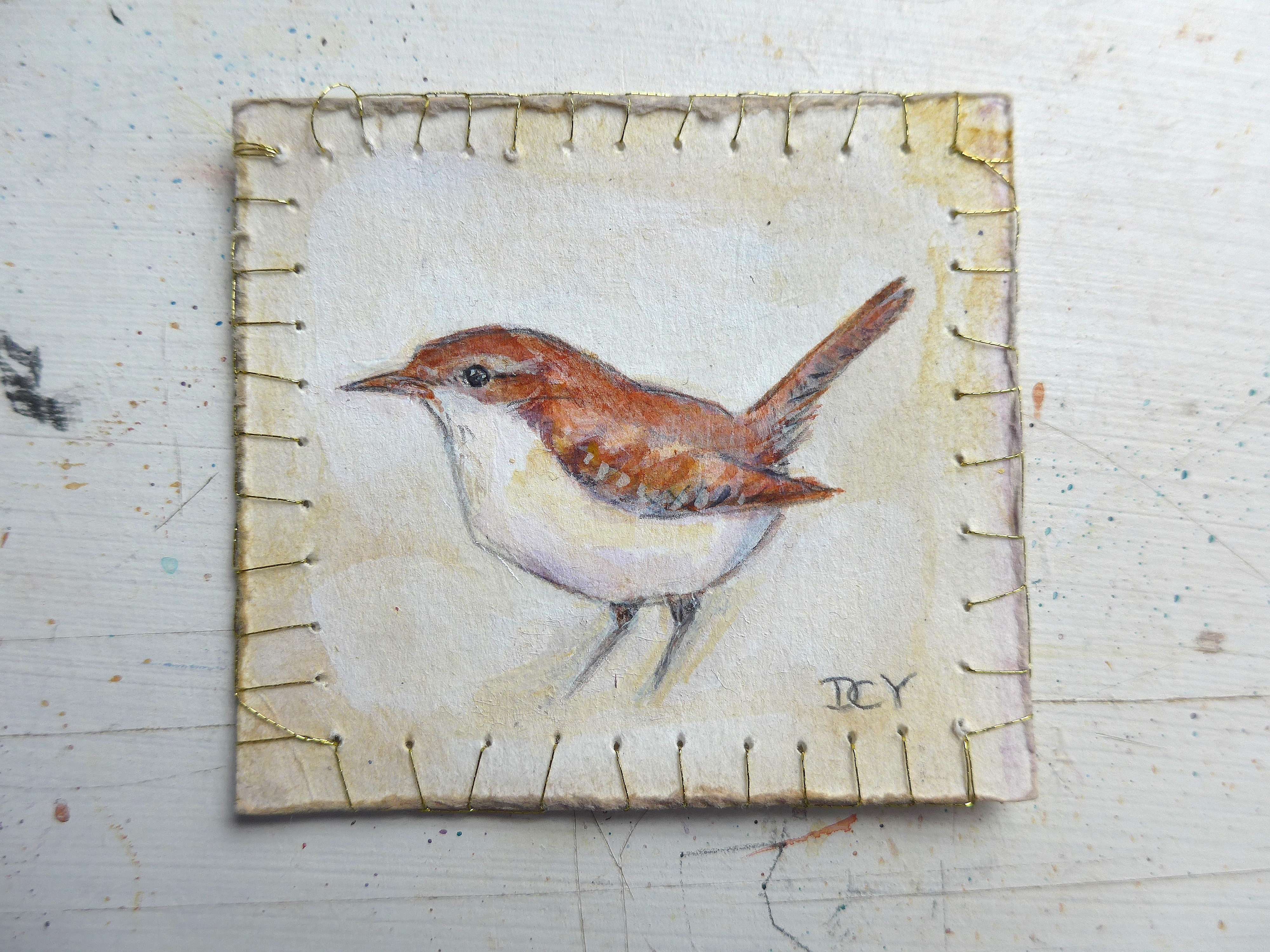 Painting showing painting of a wren on paper with gold thread decorating the edge by artist Diane Young
